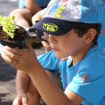 Un escolar con una planta recién sembrada en la Granja Escuela